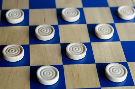 boardgames: Wooden blue and white checkers game. selective focus close up. Concept photo of business, teamwork, strategy and planning.