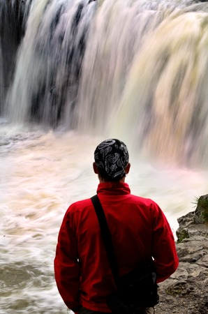 man waterfalls: A man looks at a  wild waterfalls with strong current during winter season.