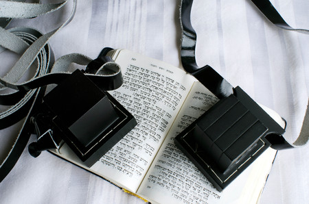 orison: A set of tefillin includes the arm-tefillin (left) and the head-tefillin on a  praying book and Tallit. Stock Photo