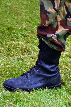 uniform green shoe: A NZ Army soldier wearing camouflage uniform - closeup on his leg and boot.