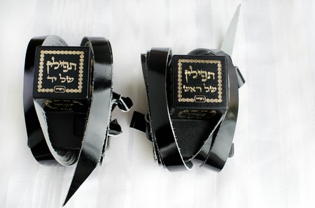 A set of tefillin includes the arm-tefillin (left) and the head-tefillin on Talit.