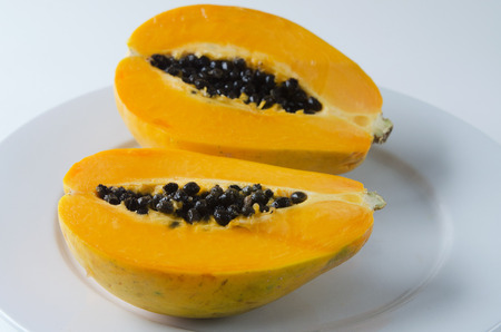 grope: Papaya or Pawpaw fruit sliced in half isolated on a white background and white plate.