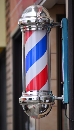 barber: American barber pole sign with a helical stripe (red, white, and blue ) on a wall of a Barbers shop.