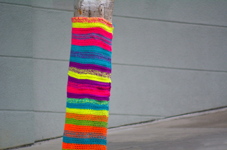 bombing: Tree trunk covered with crochet in the street. concept copy space