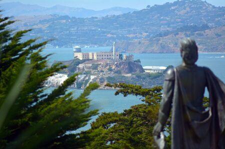 Statue of Columbus looks at Alcatraz Island in San Francisco bay, California.