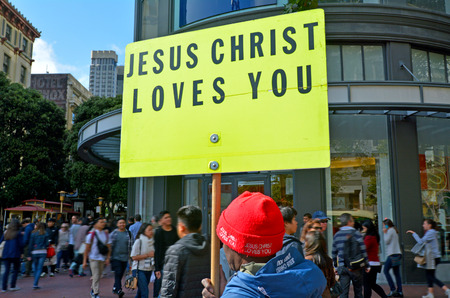 adherents: SAN FRANCISCO - MAY 17 2015:Christian man holds a Jesus Christ Love You sign during a protest.As of 2010, Christianity was by far the worlds largest religion, with an estimated 2.2 billion adherents.