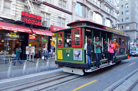 majority: SAN FRANCISCO - MAY 19 2015:Passengers riding on Powell-Hyde line cable car in San Francisco, CA.The vast majority of their 7 million annual passengers are tourists
