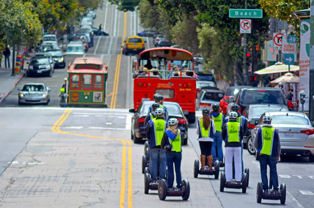 however: SAN FRANCISCO - MAY 17 2015:Segway PT tours in San Francisco.In 2002 the city banned the Segway PT from safety concerns, However, Segway Tour operations use them in cycle lanes and designated trails.