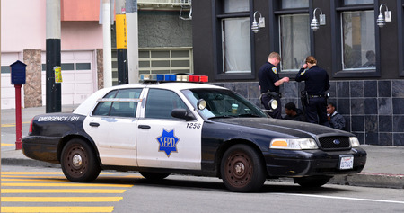 interrogating: SAN FRANCISCO - MAY 15 2015:SFPD officers interrogating black american men in San Francisco.Overall, Black Americans are arrested at 2.6 times the per-capita rate of all other Americans.