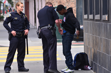 pat down: SAN FRANCISCO - MAY 15 2015:SFPD officers patdown black american man in San Francisco.Overall, Black Americans are arrested at 2.6 times the per-capita rate of all other Americans.
