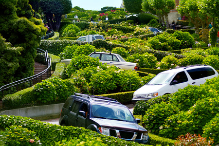 make known: SAN FRANCISCO - MAY 20 2015:Cars drive down Lombard Street switchback.Lombard Street is known for the one-way block on Russian Hill where 8 sharp turns make it the most crooked street in the world.