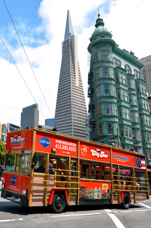 transamerica: SAN FRANCISCO - MAY 19 2015:Tour bus in San Francisco financial district, CA.The tourism industry generate $500M in taxes for the City as visitor spending over $20 million a day. Editorial
