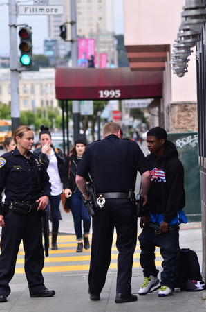 pat down: SAN FRANCISCO - MAY 15 2015:SFPD officers Frisking black american man in San Francisco.Overall, Black Americans are arrested at 2.6 times the per-capita rate of all other Americans.