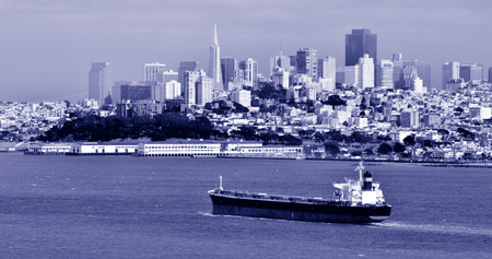 transamerica: SAN FRANCISCO - MAY 15 2015:Cargo ship with San Francisco skyline.The average depth of the San Francisco Bay is only 12-15 feet deep. Large ships in the bay must follow deep underwater channels