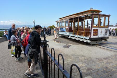 file d attente: SAN FRANCISCO - 16 mai 2015: Les passagers de la ligne téléphérique débarrasser à la station de plateau Wharf front de mer à propulsion manuelle du Pêcheur de San Francisco CA.There attente sont 2 platines à chaque extrémités. Éditoriale