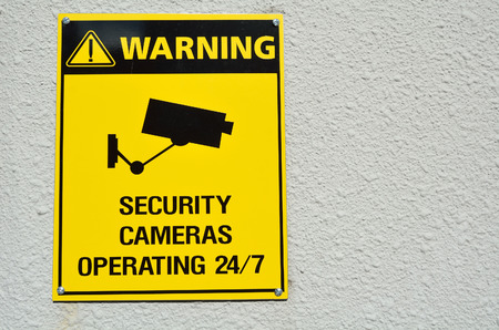 paranoia: A yellow warning cctv security cameras sign stating that there is cctv cameras in the area operating 247. concept with copyspace