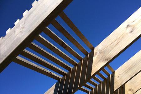 feature: Wooden pergola against blue sky of garden feature forming a shaded walkway, passageway or sitting area. Stock Photo