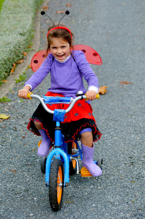 age 5: Happy little girl age 05 dressed with lady bug costume ride a bike outdoor. photo with copyspace