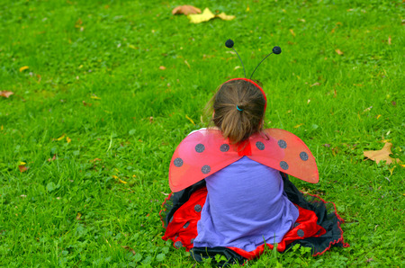dressed up: Sad little girl age 05 dressed up as lady bug sit on green grass in the garden.Concept photo with copyspace