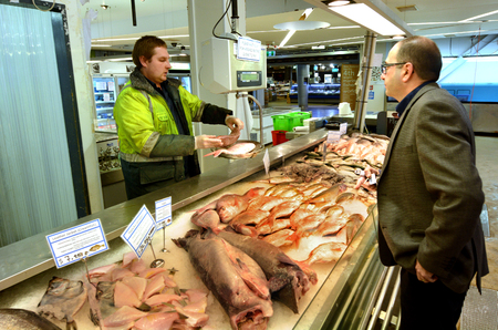 retailers: AUCKLAND - JULY 08 2015:Trade in Auckland Fish Market in Auckland New Zealand.The Fish Market building, hosts fresh seafood retailers, a boutique food market, restaurants and Auckland Seafood School.