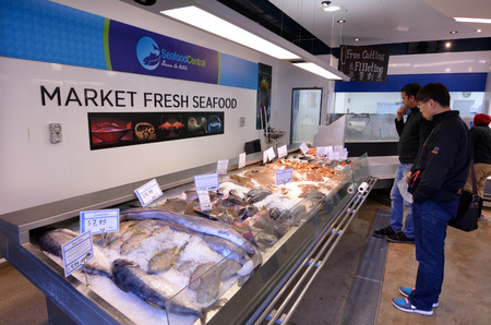 fish market: AUCKLAND - JULY 08 2015:Shoppers in Auckland Fish Market, Auckland New Zealand.The Fish Market building, hosts fresh seafood retailers, a boutique food market, restaurants and Auckland Seafood School.