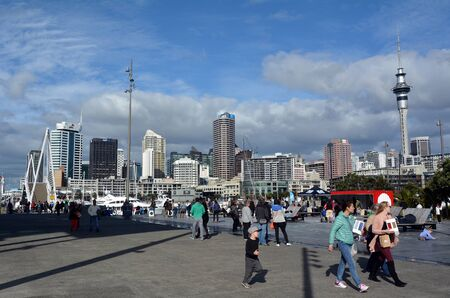ethnically diverse: AUCKLAND - AUG 01 2015:Visitors walks at Wynyard Quarter against  Auckland skyline New Zealand. Auckland is one of the most ethnically diverse cities in the world.