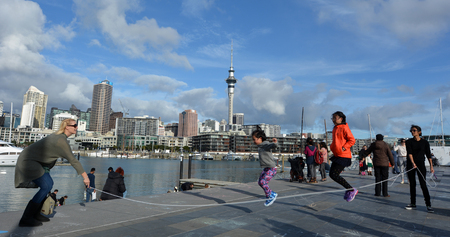 ethnically diverse: AUCKLAND - AUG 01 2015:Mixed race people jumps on a rope in  Wynyard Quarter against  Auckland skyline New Zealand. Auckland is one of the most ethnically diverse cities in the world.