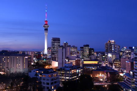 zealand: AUCKLAND - AUG 03 2015:Panoramic view of Auckland Sky tower skyline in colors at dusk.Auckland is frequently ranked within the worldÕs top 10 most liveable cities