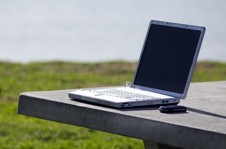 délivrance: Concept photo of a laptop on a table of an outdoor office. Banque d'images