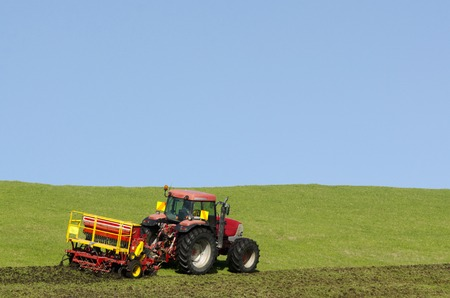 farm implements: Red tractor plowing the ground in the autumn. Stock Photo
