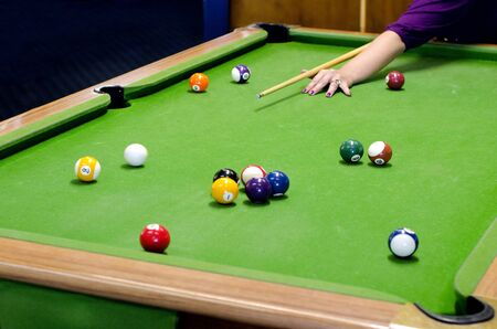 pool game: A hand of a woman player on a pool table plays pool game (Pocket Billiards).