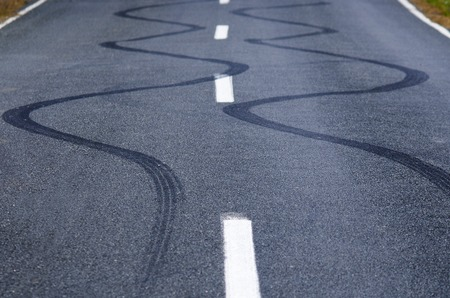 tire marks: Winding skid marks of a vehicle on a street road.