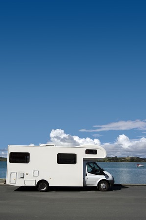 campervan: White campervan parked on a lake during road trip around New Zealand.