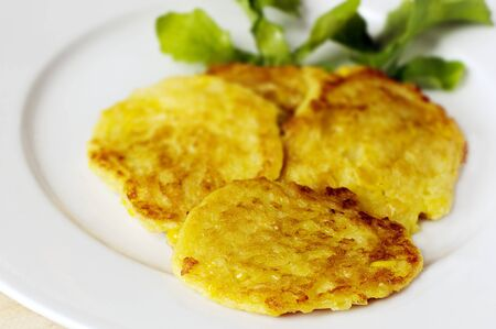 nz: NZ sweet corn fritters on white plate and rocket leaf. Stock Photo