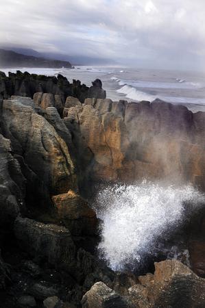blowhole: Surf of Tasman Sea exploding in blowhole in pancake rocks at Punakaiki, South Island, New Zealand.