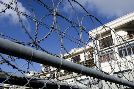 gated: Gated community apartments building behind barb wire and razor fence. Stock Photo