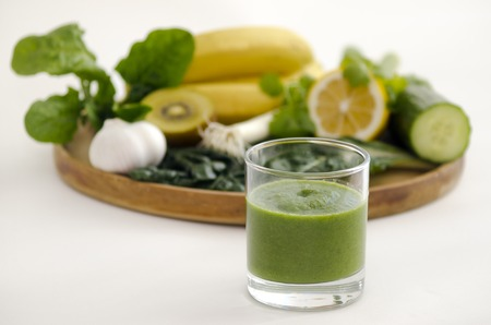 alkaline: Green smoothie alkaline diet drink beside a wooden tray with alkaline diet vegetables and fruits: Banana, kiwi, spinach, lemon, cucumber, parsley , silver beat and garlic.