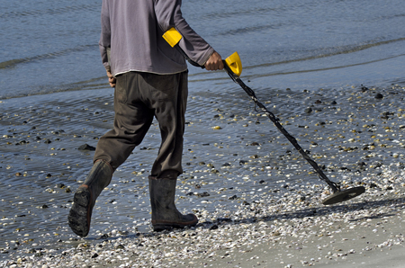 metal detector: Man using a metal detector on the beach.