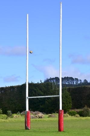 pelota rugby: Bola de rugbi que pasa a través de postes de la meta para el fútbol, ??rugby o liga en el campo. Foto de archivo