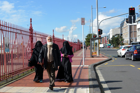 burqa: AUCKLAND,  NZL - AUG 10 2015:Muslim man walks with two muslim woman with fully body cover (Burqa).There is a great debate in New Zealand if burqa should not be allowed in certain situations.