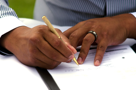 registry: Groom signing marriage license or wedding contract. close-up