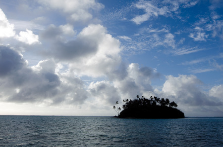 rarotonga: Silhouette of a small coral islet at Muri Lagoon in Rarotonga Cook Islands during sunrise. Stock Photo