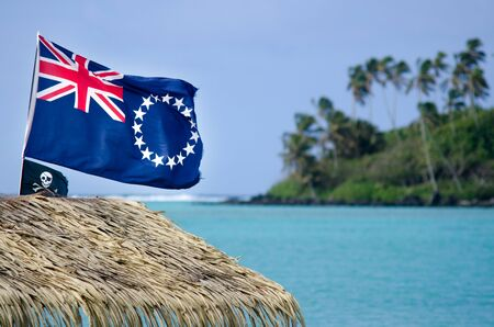 jolly roger: The Cook Islands national flag and Jolly Roger pirates flag wave in the wind at Muri Lagoon in Rarotonga Cook Islands.