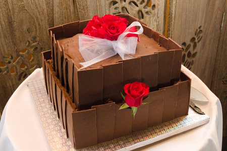 wedding table decor: Wedding cake made out of chocolate decorated with red rose.