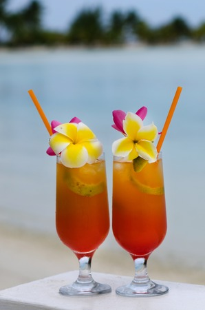 tropical drink: Tropical cocktails served outdoor on Pacific Island resort with turquoise water in the background.