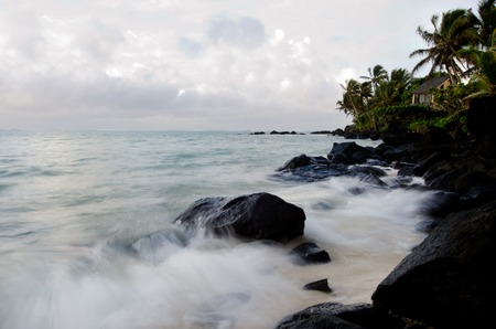 rarotonga: Sea waves breaks on black rocks at Muri Lagoon in Rarotonga Cook Islands during sunrise.