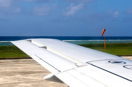 windsock: Wing of an airplane during taking off and landing in Airport. People looks outside from the window of the plane, using air transport to travel. Stock Photo