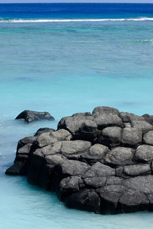 ancestors: Black Rock, or Touro, legendary departure place of the deceased souls of the Cook Islanders, Polynesians ancestors. Today its a famous landmark and popular swimming place in Rarotonga, Cook Islands. Stock Photo
