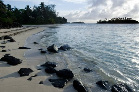 rarotonga: Black rocks at Muri Lagoon in Rarotonga Cook Islands during sunrise. Stock Photo