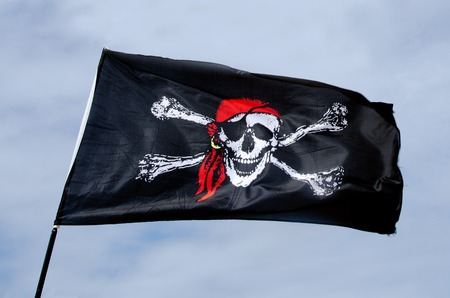 roger: Jolly Roger, Pirates flag against blue sky. Stock Photo